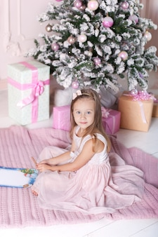 Petite fille écrit une lettre au père noël près de l'arbre de noël