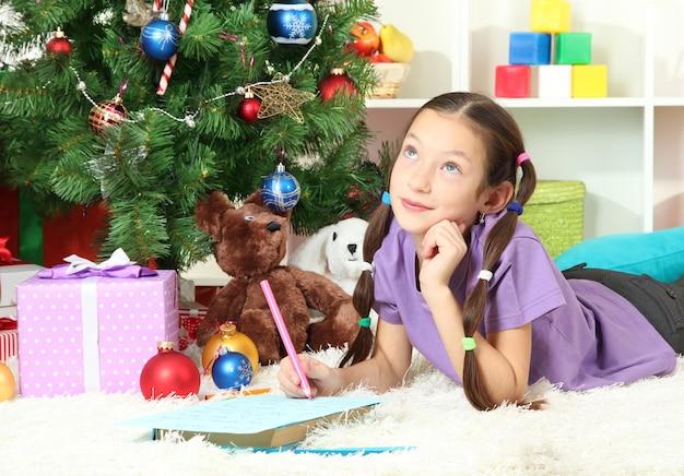 Petite fille écrivant une lettre au père noël près de l'arbre de noël