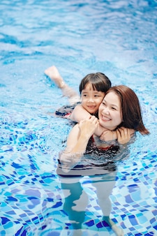 Petite fille effrayée étreignant sa mère car elle a peur de nager dans la piscine