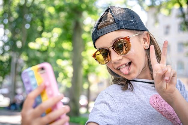 Petite fille élégante à lunettes de soleil prenant un selfie à l'extérieur.