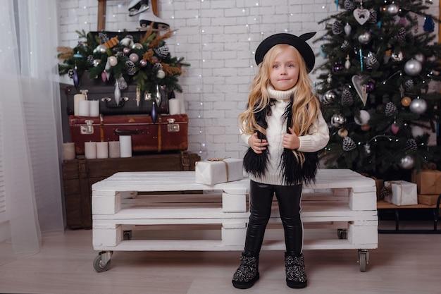 Petite fille élégante posant près de l'arbre du nouvel an en prévision de noël.