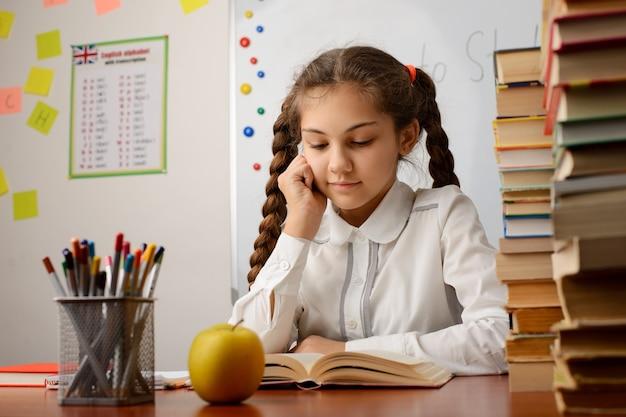 Petite fille élève de l'école élémentaire lisant un livre étudiant en classe
