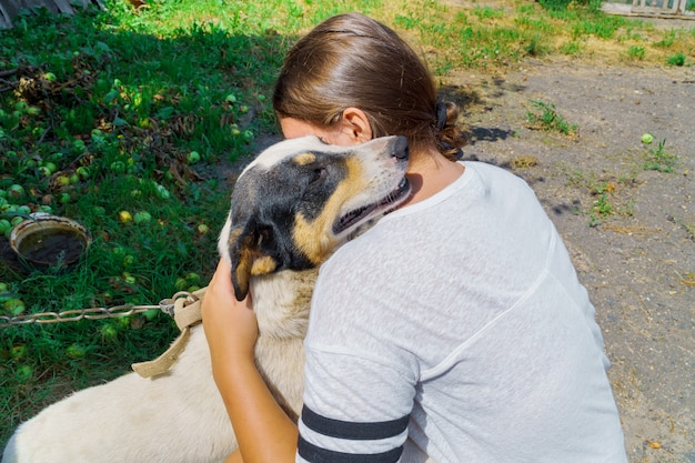 Petite fille embrassant un chien en plein air