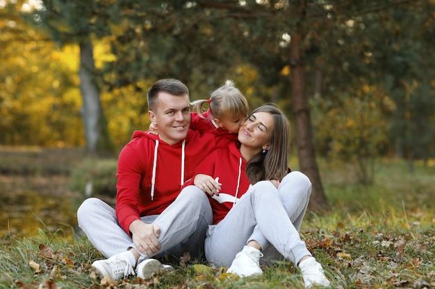 Petite fille embrassant et étreignant sa maman et son père dans le parc en automne