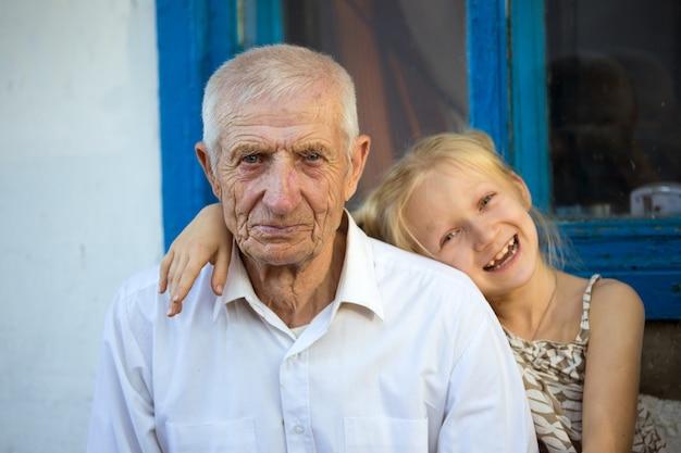 Petite-fille embrassant avec les grands-parents assis à l'avant de la maison rurale