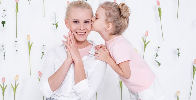 Petite fille embrassant une mère heureuse