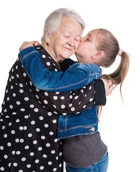 Petite-fille embrassant sa grand-mère sur un mur blanc