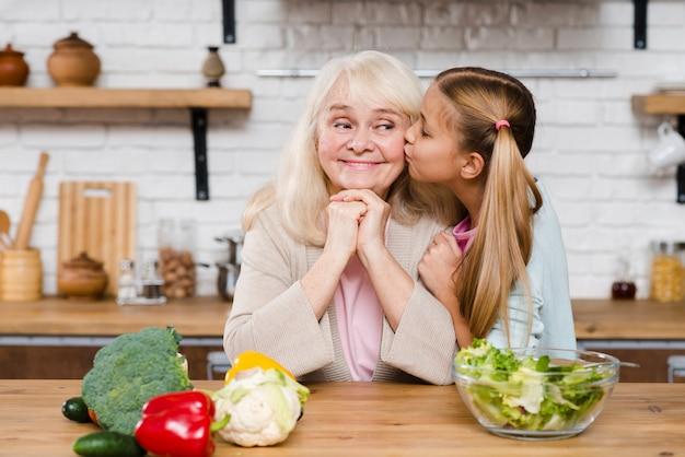 Petite-fille embrassant sa grand-mère sur sa joue
