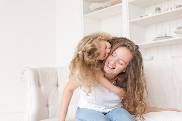 Petite fille embrassant sa mère à l'intérieur