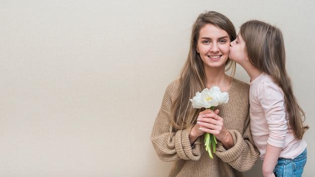 Petite fille embrassant sa mère avec des tulipes sur la joue