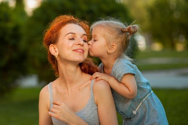 Petite fille embrasse sa mère dans la nature