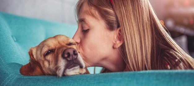 Petite fille embrasse son chien sur un canapé