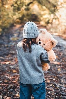Petite fille embrasse son ours dans la nature