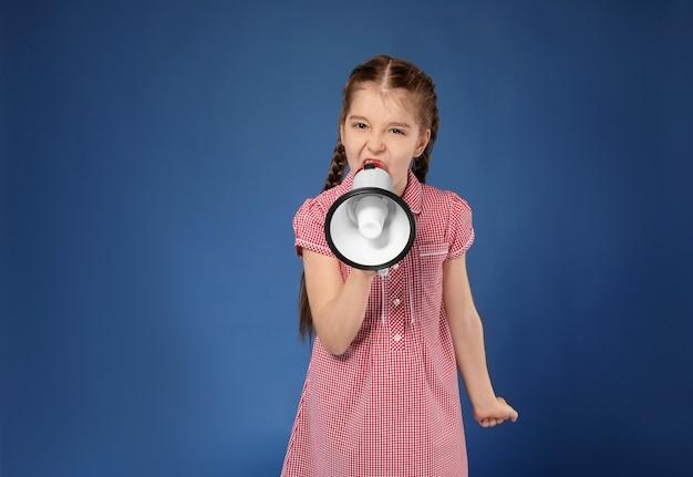 Petite fille émotionnelle criant dans un mégaphone sur la couleur