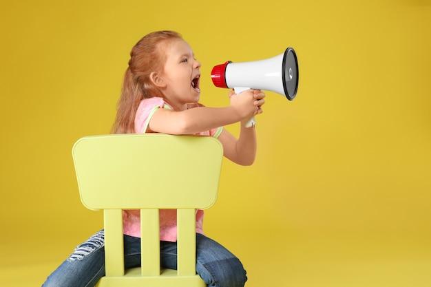 Petite fille émotionnelle avec mégaphone assis sur une chaise contre la couleur