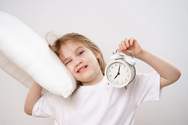 Une petite fille endormie embrasse un oreiller et un réveil sur fond blanc.