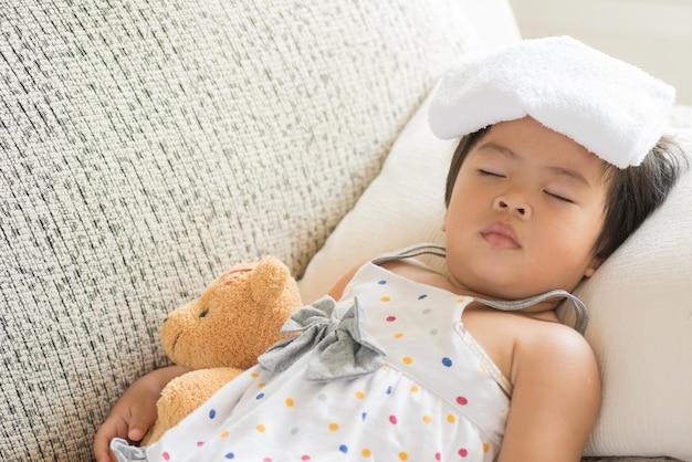 Petite fille endormie et malade sur le canapé avec un gel plus froid sur la tête et mesurant son tempérament