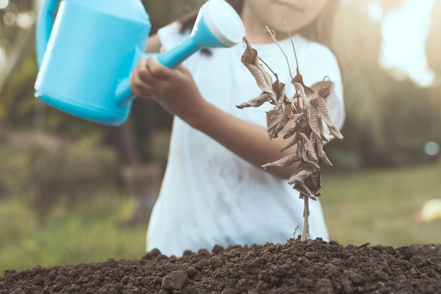 Petite fille enfant arrosant un arbre sec avec arrosoir dans le ton de couleur vintage