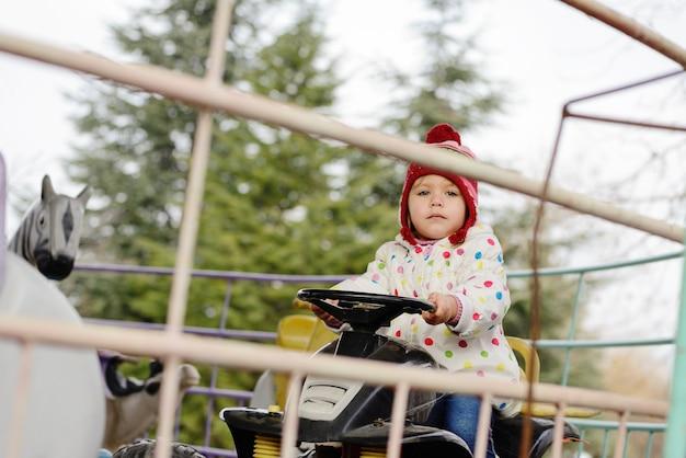 Petite fille enfant en bas âge à cheval sur une voiture drôle sur un carrousel rond-point dans un parc d'attractions