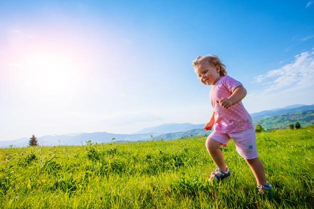 Petite fille enfant en bas âge en cours d'exécution dans un beau champ