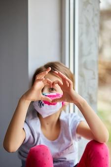 Petite fille, enfant, dans, masque, confection, cœurs, depuis, mains, coronavirus, quarantaine