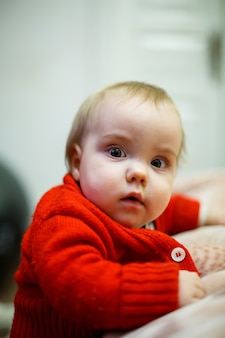 Petite fille enfant dans un pull rouge, son visage est sale avec de la nourriture, beau bokeh