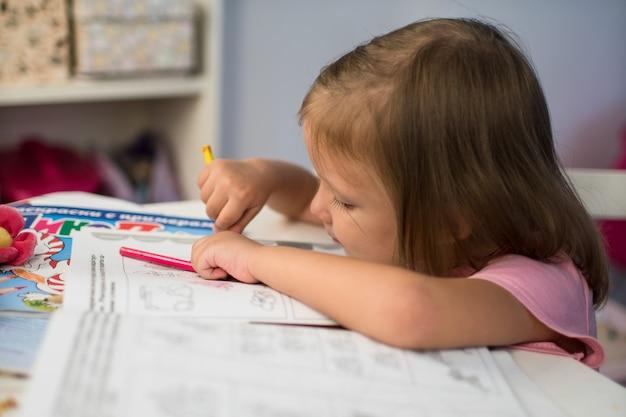 La petite fille d'enfant dessine des crayons à la maison