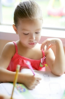 Petite fille enfant écrit au bureau de l'école
