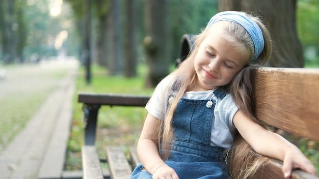Petite fille enfant fatiguée assise sur un banc avec les yeux fermés au repos dans le parc d'été.