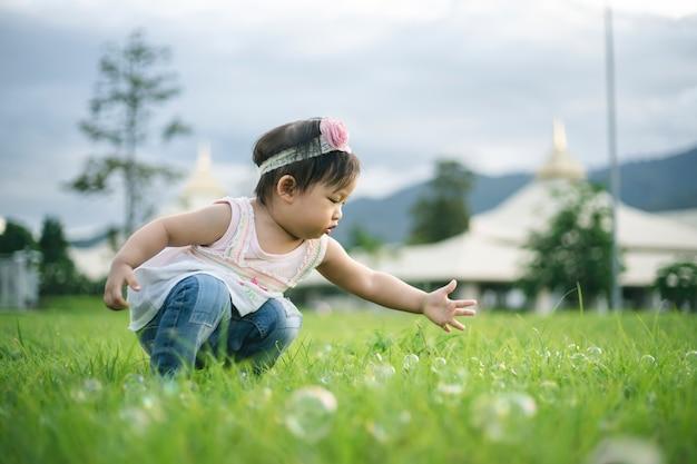 Petite fille enfant jouant avec des bulles sur l'herbe verte à l'extérieur dans le parc.