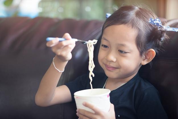 Petite fille enfant mange tasse de nouilles avec heureux.