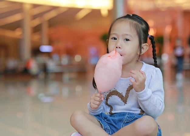 Petite fille enfant mangeant des bonbons spongieux sucrés