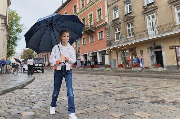 Petite fille enfant marchant avec un parapluie dans une rue de la ville