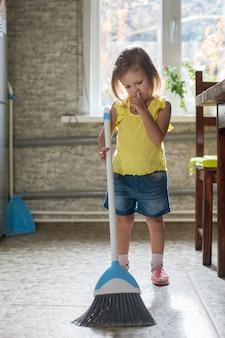 La petite fille d'enfant nettoie la maison dans la cuisine et met son doigt dans le nez