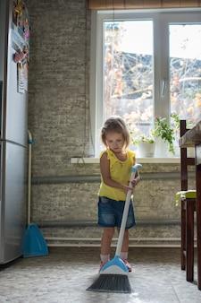 La petite fille d'enfant nettoie la maison dans la cuisine