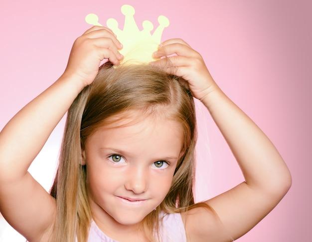 Petite fille enfant reine avec couronne en or.