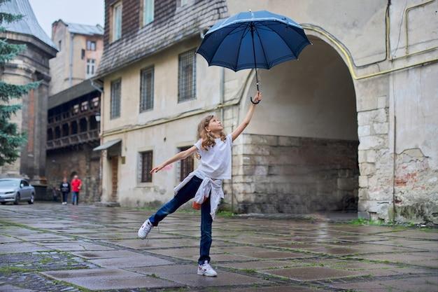 Petite fille enfant sous la pluie avec un parapluie, fond de vieille ville touristique