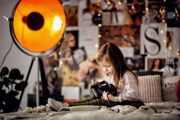 Petite fille enfantine examine un appareil photo dans ses mains dans un photostudio sur un lit