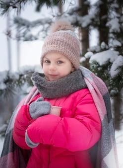 Petite fille enveloppée dans une couverture de boire du thé dans la forêt d'hiver