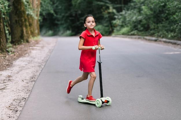 Petite fille, équitation, pousser, scooter, sur, route