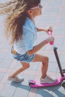 Petite fille équitation scooter à l'extérieur. rue urbaine