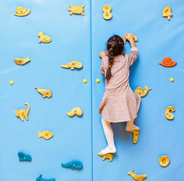 Petite fille escaladant un mur de pierre intérieur