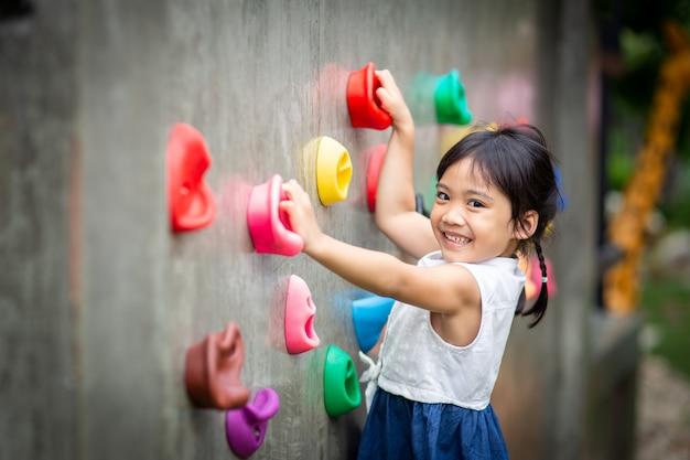 Petite fille escaladant un mur de pierre