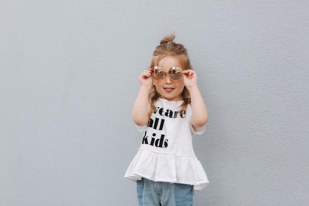 Petite fille essaie des lunettes de soleil et pose au photographe.