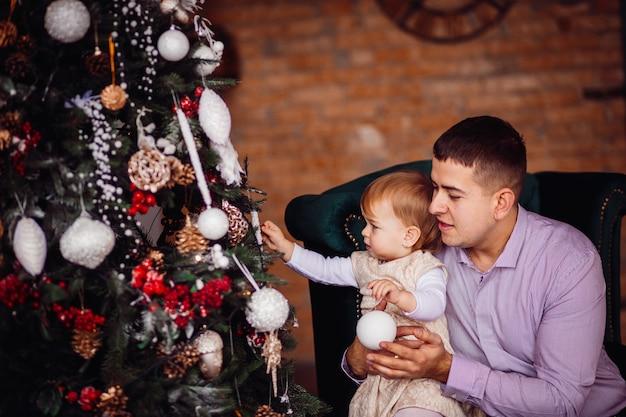 Petite fille essaie de toucher le jouet assis avec papa devant un arbre de noël