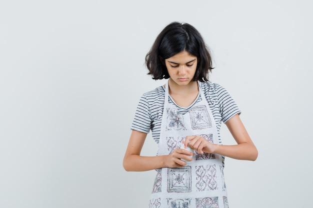 Petite fille essayant d'ouvrir la bouteille de pilules en t-shirt