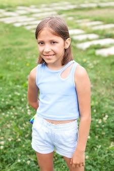 Une petite fille est allongée sur l'herbe dans le parc un jour d'été. il sourit et regarde la caméra. enfance heureuse.