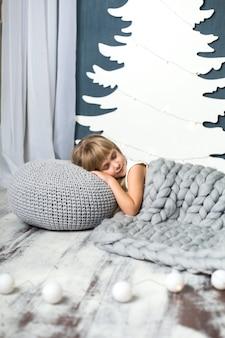 La petite fille est allongée sur un oreiller recouvert d'une couverture tricotée grise contre un décor artificiel de sapin de noël blanc en carton. à côté se trouve une guirlande.