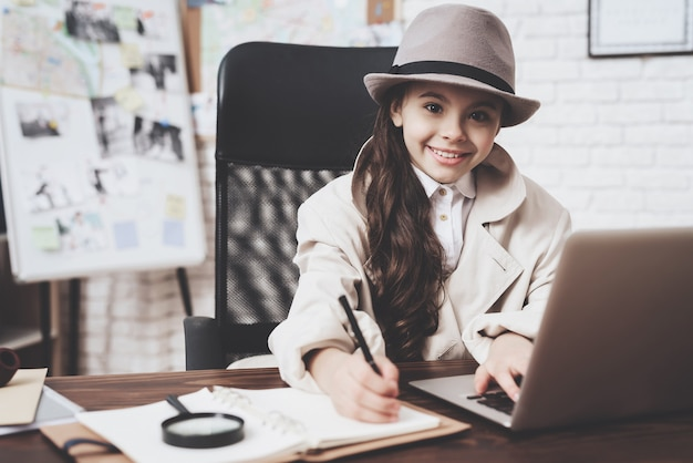 Petite fille est assise au bureau, prenant des notes près d'un ordinateur portable.