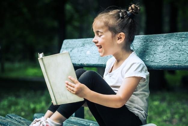 Petite fille est assise sur un banc et lit un livre